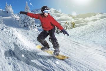 Snowboarder fährt bergab in sonniger Winterlandschaft