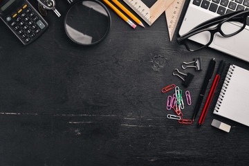 Office desktop, Laptop, notebook, pen. On a black background. Top view. Free space for text. Copy space.