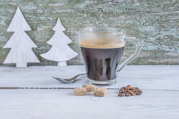 glass cup of hot coffee on rustic background with christmas decoration
