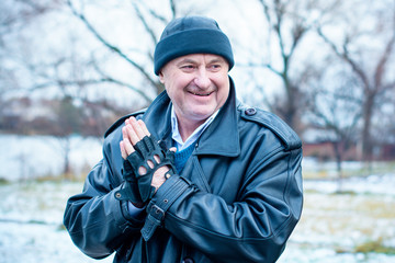 American Mature Happy Man Smiling with good mood at nature outside. Portrait of happy elderly man against winter forest background on a travelling