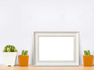 white wooden frame with cactus in pot on wood table