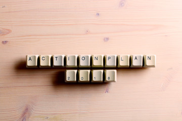 Action plan 2018 on computer keyboard keys buttons on a wooden background