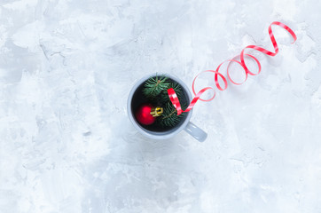 Fir toy, fir branches and cup on concrete background
