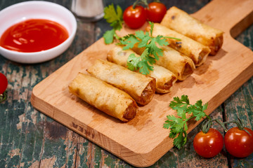 Vietnamese food. Delicious homemade spring rolls on wooden table.