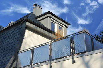 Edelstahlbalkon, mit rechteckigen schwarzen Kunststoffschindeln neu eingedecktes Dach mit metall-verkleideter Gaube und Schornstein mit Edelstahl-Kragen/-Dach und modernem Schneefang