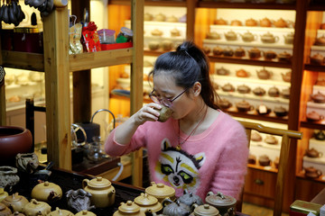 "An owner of a family tea-ware shop drinks tea as handmade red clay pots are seen in the background, in Dingshu town, Yixing city, known as ""pottery city"