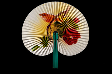 Closeup of Traditional Chinese fan on black background.