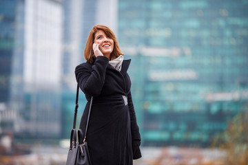Image of girl in black coat talking on phone