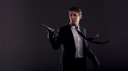 Image of man with developing tie in leather gloves with gun