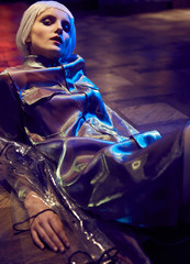 Futuristic neon lighted portrait of a girl with white bob hairstyle wearing silky blouse and transparent raincoat sitting on the floor