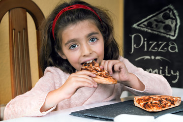 happy little girl eating pizza in a restaurant / girl holding slice of pizza barbecue in house