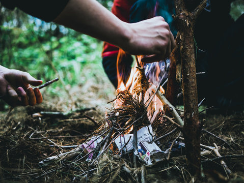 close up shot of man making a fire in the forest