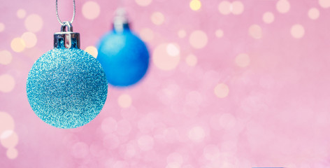 Photo of two Christmas blue balls on pink background with spots.