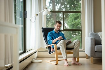 Man reading a book in living room