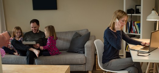 Mother using laptop while father and daughters using digital