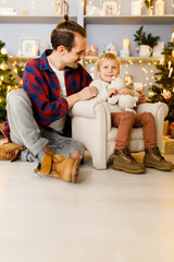 Holiday picture of son on chair and happy dad
