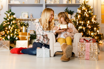 New Year's picture of mother giving gift to daughter sitting on chair against backdrop of scenery, Christmas tree