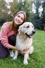 Portrait of brunette hugging labrador on lawn in summer park