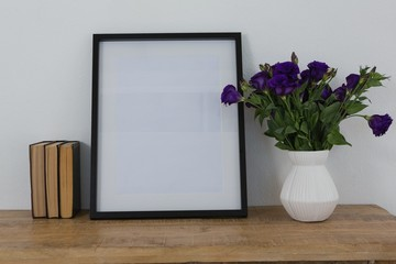 Picture frame and flower vase on table