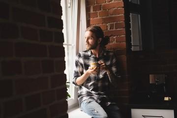 Thoughtful man having coffee near window