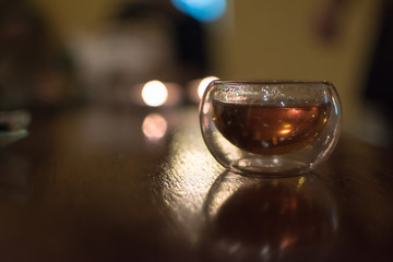 Transparent small glass of Chinese black tea on a table, shot contre-jour to candlelight