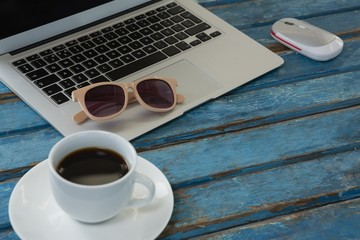 Laptop, black coffee, sunglasses and mouse on wooden plank