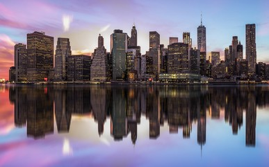 NEW YORK, UNITED STATES OF AMERICA - APRIL 28, 2017: New York City Manhattan skyline panorama with skyscrapers building in at dusk illuminated with lights at sunset