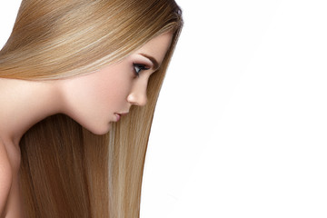 Beautiful blond girl with a perfectly smooth hair, and classic make-up. Beauty face. Picture taken in the studio.