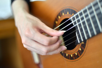 Female hand playing on electric guitar close up.