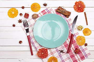 Festive table setting with cutlery, dried oranges and spices on white wooden table. Top view.