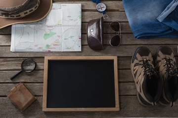 Apparels and travelling accessories on wooden plank