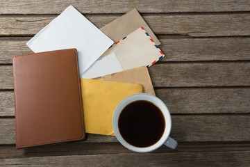 Coffee with various envelopes and diary on wooden plank