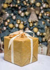 Yellow gift box and decorated New Year Tree on the background.