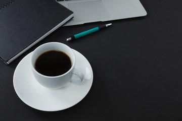Pen, organizer, black coffee and laptop on black background