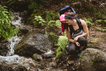 Mother and daughter looking at flowing stream
