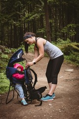 Mother adjusting backpack carrier while hiking