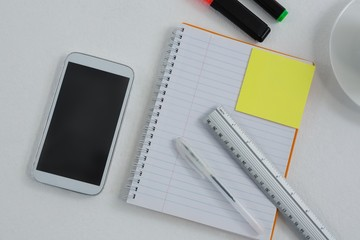 Mobile phone and stationery on white background