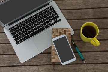 Laptop, mobile phone, dairy, pen and coffee on wooden plank
