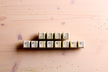 Upcoming New year 2018 on computer keyboard keys buttons on a wooden background