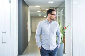 Business man standing in office with arms in pockets and looking away.