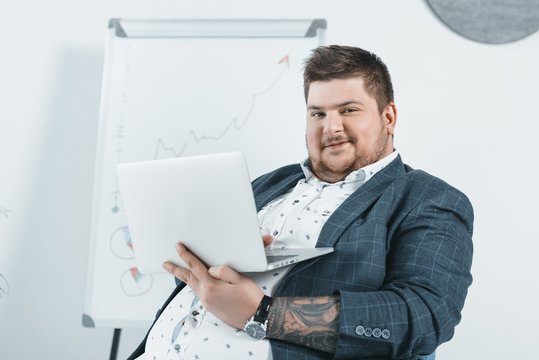 overweight businessman in suit working with laptop in office