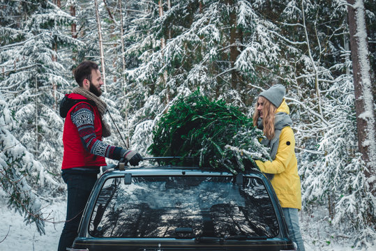 Caucasian couple tying fresh cut Christmas tree to a roof of a vintage SUV. Lifestyle, celebration, relationship concept