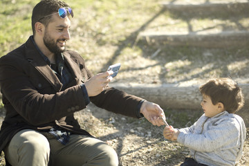 Father taking photo with smartphone to his baby boy while playing with wood stick