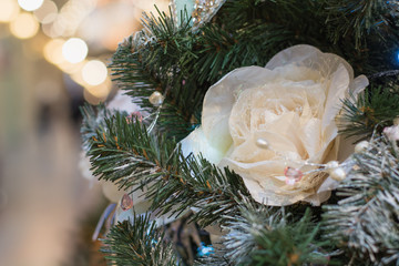 Decorated Christmas tree flowers and lights with copy space on bokeh background in interiors. Close up. Xmas.