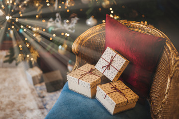 Three wrapped present boxes on armchair near Christmas fir tree. Design or idea for postcard. New Year composition with decorated fir tree and gifts. Majestic atmosphere. Festive event