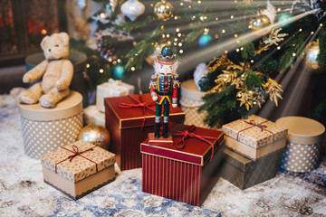 Many gifts under decorated New Year tree. Home interior and festive atmosphere. Winter holidays concept. Horizontal picture with many wrapped gifts. Calm atmosphere and festive event.