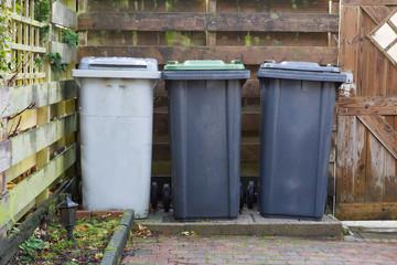 Three rolling trash cans in a dutch garden