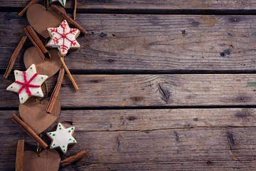 Cinnamon sticks, cookies and christmas decoration on wooden