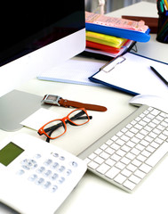 Office table with blank notepad and laptop