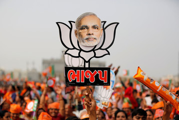 A supporter holds up a cut-out of lotus, the election symbol of India's ruling BJP, with an image of PM Modi during a campaign meeting addressed by Modi ahead of Gujarat state assembly election in Kalol